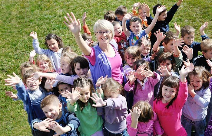 Leerkracht met blije kinderen